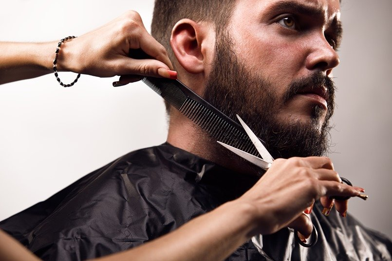 a man getting his beard professionally groomed in order to maintain proper beard care