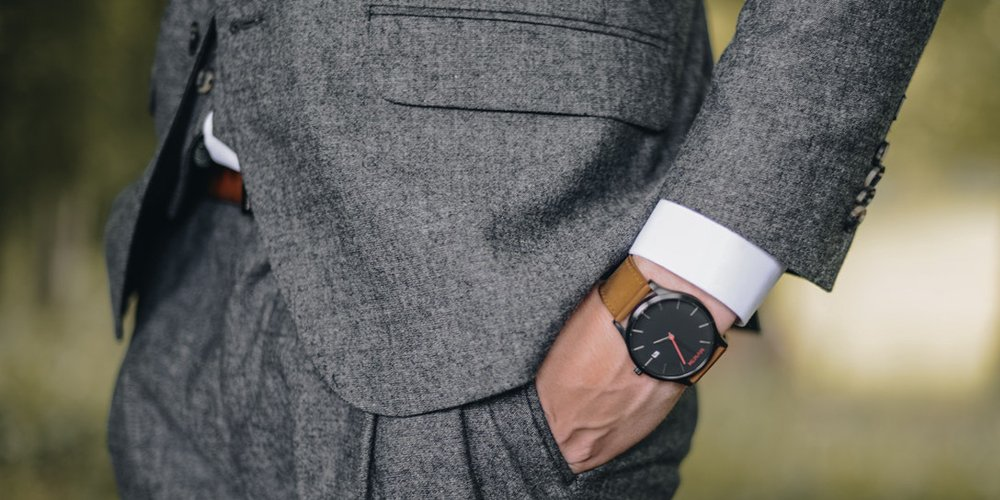 a man in a gray suit wearing his watch on the left hand
